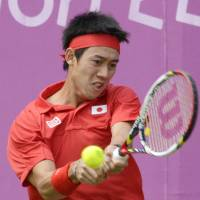 Back at you: Kei Nishikori plays a shot to Bernard Tomic during their match on Sunday in London. | KYODO