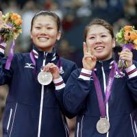 Silver lining: Reika Kakiiwa (left) and Mizuki Fujii celebrate on the medal stand after finishing second in the women's badminton doubles competition on Saturday in London. | AP