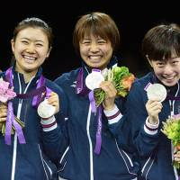 Trailblazers: Ai Fukuhara, Sayaka Hirano and Kasumi Ishikawa display their silver metals and savor their moment of glory as Japan's first medal winners in table tennis. China's team took the gold in Tuesday's final. | KYODO PHOTO