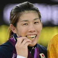 Wrestler Saori Yoshida sinks her teeth into her third consecutive Olympic gold in the women's 55 kilograms category. | KYODO PHOTO