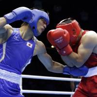 Packing a powerful punch: Ryota Murata works over Uzbekistan's Abbos Atoev in their middleweight semifinal bout on Friday at ExCel Arena. Murata won a 13-12 decision. | AP