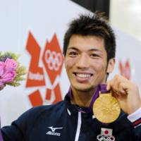 Black, blue, and gold: Ryota Murata shows off his gold medal after defeating Brazilian boxer Esquiva Falcao Florentino in the middleweight final. | KYODO