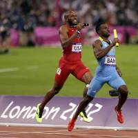 David beats Goliath: Ramon Miller of the Bahamas passes Angelo Taylor of the United States in the homestretch to win the gold in the 4x400-meter relay at the Olympic Stadium on Friday night. | AP