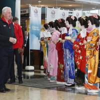 Warm welcome: International Olympic Committee Vice President Craig Reedie of Britain (second from left) is greeted by kimono-clad models as he visits the Big Sight in Tokyo on Wednesday. | AP