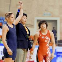 Athens Olympics gold medal-winning wrestler Saori Yoshida, right, reacts after losing to the United States' Marcie Van Dusen in the 55-kg weight category at an international World Cup team competition on Saturday in Taiyuan, China. Yoshida's win streak ended at 119 matches. | KYODO PHOTO
