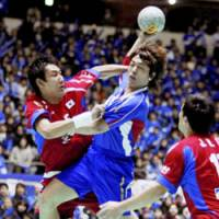 Japan's Daisuke Miyazaki (center) takes a shot during a game against South Korea in a replay of the men's handball qualifying tournament for the Beijing Olympics at Tokyo's Yoyogi National Gymnasium on Wednesday. Japan lost 28-25. | KYODO PHOTO
