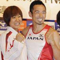 Golden smiles: Long-distance runner Yoko Shibui and 400m-hurdler Dai Tamesue celebrate making Japan's track and field Olympic team in Kawasaki on Monday. | KYODO PHOTO