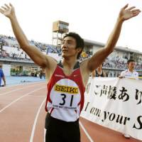 Fond farewell: Four-time Olympian Nobuharu Asahara waves to the fans after competing in the final 100-meter race of his career on Tuesday at Todoroki Stadium in Kawasaki. | KYODO PHOTO