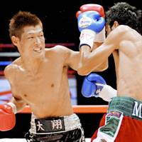 Seventh defense: WBC bantamweight champion Hozumi Hasegawa (left) lands a left hook against Alejandro Valdez of Mexico during the second round of their title bout on Thursday at Yoyogi National Gymnasium in Tokyo. Hasegawa scored a technical knockout in the second. | KYODO PHOTO