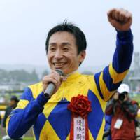Delightful day: Jockey Norihiro Yokoyama, who guided Logi Universe to a four-length victory in the Japan Derby, enjoys the spotlight on Sunday at Tokyo Racecourse. | KYODO PHOTO