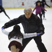 Wisdom for the ages: Veteran coach and two-time Olympian Nobuo Sato works with seven-year-old skater Rurino Tsuru at the Shin-Yokohama Skate Center on Monday. | AP PHOTO