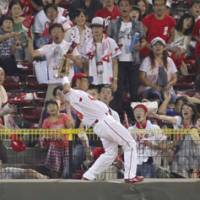 What a catch: Hiroshima Carp outfielder Soichiro Amaya's wall-climbing catch is going to be replayed on highlight reels for years to come. | KYODO PHOTO