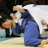 Century mark: Yoshie Ueno unleashes a throw against Miki Tanaka in the women's 63-kg final at the world judo championships Saturday in Tokyo. Japan won its 100th overall world championship gold during the event. | KYODO PHOTO