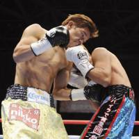 Textbook punch: Daiki Kameda (left) gives a body blow to Takefumi Sakata on Saturday. Kameda defended his WBA flyweight title, defeating his compatriot by unanimous decision at Tokyo Big Sight. | KYODO PHOTO
