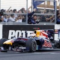 Day to celebrate: Red Bull driver Sebastian Vettel crosses the finish line to win the Japanese Grand Prix at the Suzuka Circuit on Sunday. | AP PHOTO