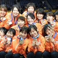 Team Japan celebrate their win Sunday over the United States, which earned them a bronze medal at the women's volleyball world championship. | KYODO PHOTO