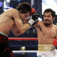 Fight night: Manny Pacquiao, right, solidified his spot atop the boxing world by delivering a beating to Antonio Margarito during their WBC light middleweight title bout on Saturday. | AP PHOTO