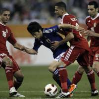 Safety in numbers: Shinji Kagawa is surrounded by four Jordan players during Japan's opening game of the Asian Cup in Doha on Sunday. | AP PHOTO