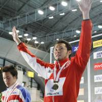 Victory lap: Kosuke Kitajima waves to the crowd after his record-setting swim on Sunday. | KYODO PHOTO