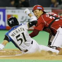 Back to work: Rakuten's Motohiro Shima, right, Nippon Ham's Kazuya Murata and the rest of the NPB are slated to begin the season on Tuesday. | KYODO PHOTO