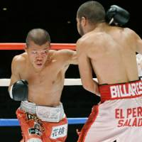On the attack: Koki Kameda punches challenger David De La Mora during their WBA bantamweight title bout on Wednesday in Tokyo. Kameda retained his title by unanimous decision. | KYODO