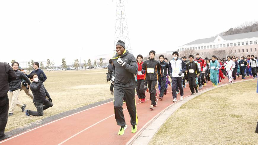 Getting pointers from a superstar: Olympic legend Carl Lewis trains with youth athletes on Sunday as part of the two-day 'Tohoku Sports Summit.' COURTESY