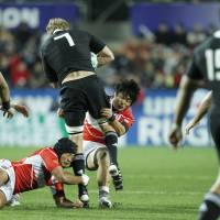Overwhelmed: Japan hooker Yusuke Aoki (left) and flanker Itaru Taniguchi tackle All Blacks flanker Adam Thomson at the Rugby World Cup on Friday. New Zealand beat Japan 83-7. | AKI NAGAO