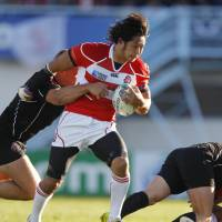 Valiant effort: Japan wing Kensuke Endo breaks through the Canadian defense at the Rugby World Cup in their Pool A match on Tuesday. The teams fought to a 23-23 draw. | AKI NAGAO