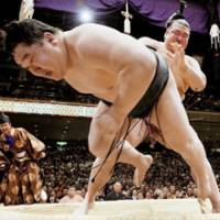 Top-ranked maegashira Kisenosato sends yokozuna Asashoryu out of the ring on the second day of the New Year Grand Sumo Tournament at Tokyo's Ryogoku Kokugikan on Monday. | KYODO PHOTO