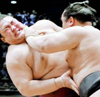 Yokozuna Asashoryu (right) pushes komusubi Kisenosato on Sunday during the first day of the Spring Grand Sumo Tournament at Osaka Prefectural Gymnasium. | KYODO PHOTO