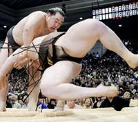 Yokozuna Asashoryu throws down yokozuna rival Hakuho to win his first Emperor's Cup in four tournaments and 22nd overall on Sunday in final-day action of the Spring Grand Sumo Tournament at Osaka Prefectural Gymnasium. | KYODO PHOTOS