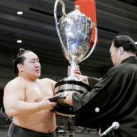 Yokozuna Asashoryu, at left, receives the Emperor's Cup on Sunday after winning the Spring Grand Sumo Tournament in Osaka, the 22nd Emperor's Cup of his colorful career.