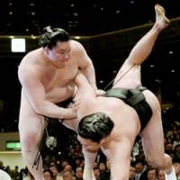 All-Mongolian battle: Yokozuna Hakuho unleashes an upper-arm throw to No. 2 maegashira Kyokutenho to stay undefeated in the Summer Grand Sumo Tournament at Tokyo's Ryogoku Kokugikan on Wednesday. | KYODO PHOTO
