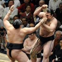 Upset: Maegashira No. 4 Aminishiki (left) hands ozeki Kotooshu his first loss of the Summer Grand Sumo Tournament at Tokyo's Ryogoku Kokugikan on Friday. | KYODO PHOTO
