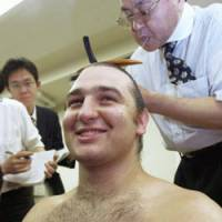 Ozeki Kotooshu speaks to the media while getting his mage (top knot of hair) reshaped after winning his first Emperor's Cup at the Summer Grand Sumo Tournament on Saturday at Ryogoku Kokugikan in Tokyo. Kotooshu became the first European to win a sumo championship. | KYODO PHOTO