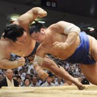 Photo finish: Yokozuna Asashoryu and third-ranked maegashira Tochinonada fall together in their bout at the Nagoya Grand Sumo Tournament at Aichi Prefectural Gymnasium on Thursday. Judges declared Tochinonada the winner. | KYODO PHOTO