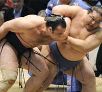Steady grip: Kaio clamps an arm lock on fellow ozeki Kotooshu before throwing him out of the ring on the penultimate day of the Nagoya Grand Sumo Tournament at Aichi Prefectural Gymnasium on Saturday. | KYODO PHOTO