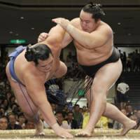Asashoryu tosses No. 1 maegashira Kotoshogiku out of the ring for his second victory on the second day of the Autumn Grand Sumo Tournament in Tokyo. | KYODO PHOTO