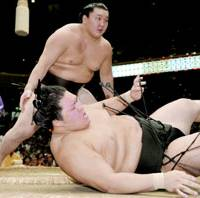 Climbing to top: Yokozuna Hakuho throws down Goeido in the battle of the wrestlers holding a 9-1 record to take the solo lead of the Autumn Grand Sumo Tournament at Tokyo's Ryogoku Kokugikan on Wednesday. Hakuho improved to 10-1 while Goeido slipped to 9-2. | KYODO PHOTO