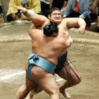 Foot fault: Toyonoshima puts his foot outside the ring just before sending ozeki Kotomitsuki flying into the crowd at Tokyo's Ryogoku Kokugikan in the Autumn Grand Sumo Tournament on Friday. | KYODO PHOTO