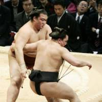 Overpowered: No. 4 maegashira Kisenosato (left) forces out Ama to hand the sekiwake his first loss of the Kyushu Grand Sumo Tournament at Fukuoka Kokusai Center on Tuesday. | KYODO PHOTO