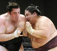 Close quarters: Miyabiyama (right) gets to grips with Kokkai during their bout at the Kyushu Grand Sumo Tournament on Monday. Miyabiyama won to keep a share of the lead with yokozuna Hakuho. | KYODO PHOTO