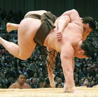 The harder they come: Sekiwake Ama sends yokozuna Hakuho crashing to the ground at the Kyushu Grand Sumo Tournament on Thursday. | KYODO PHOTO