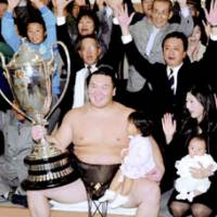 Mongolian yokozuna Hakuho celebrates his ninth career Emperor's Cup victory with family and friends on Sunday after defeating Ama in a playoff at the Kyushu Grand Sumo Tournament. Hakuho has now won three straight tournaments. | KYODO PHOTOS