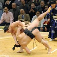 Title-clinching throw: Yokozuna Hakuho unleashes an upper-arm throw to sekiwake Ama in the championship playoff of the Kyushu Grand Sumo Tournament on Sunday at Fukuoka Kokusai Center. Hakuho and ozeki-bound Ama were tied at 13-2 after the 15-day tournament.