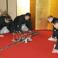 Ama (second from left) bows with stablemaster Isegahama and his wife as sumo officials notify the Mongolian wrestler of his promotion to ozeki on Wednesday in Fukuoka. | KYODO PHOTOS
