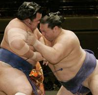 Third straight win: Ozeki Kaio (right) pushes No. 1 maegashira Kotoshogiku out of the ring for his third consecutive victory at the New Year Grand Sumo Tournament on Tuesday at Tokyo's Ryogoku Kokugikan. | KYODO PHOTO