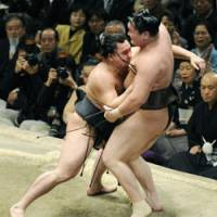 Upset: Harumafuji forces out yokozuna Hakuho to hand him his first loss at the New Year Grand Sumo on Tuesday. | KYODO PHOTO