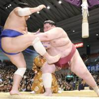 Force out: Yamamotoyama pushes Toyozakura out of the ring at the Spring Grand Sumo Tournament in Osaka on Wednesday for a share of the lead at 4-0. | KYODO PHOTO