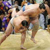 Air time: Harumafuji throws Baruto out of the ring at the Spring Grand Sumo Tournament on Thursday. | KYODO PHOTO